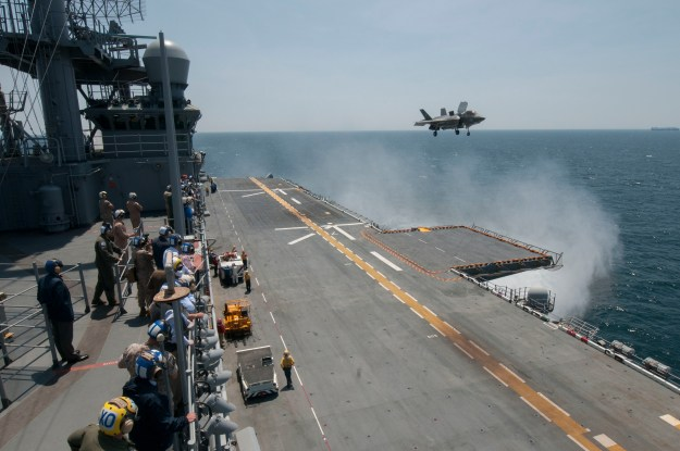 Sailors and distinguished visitors watch an F-35B Lightning II aircraft conduct vertical takeoff and landing flight operations aboard the amphibious assault ship USS Wasp (LHD 1) on May 20, 2015. US Navy photo.
