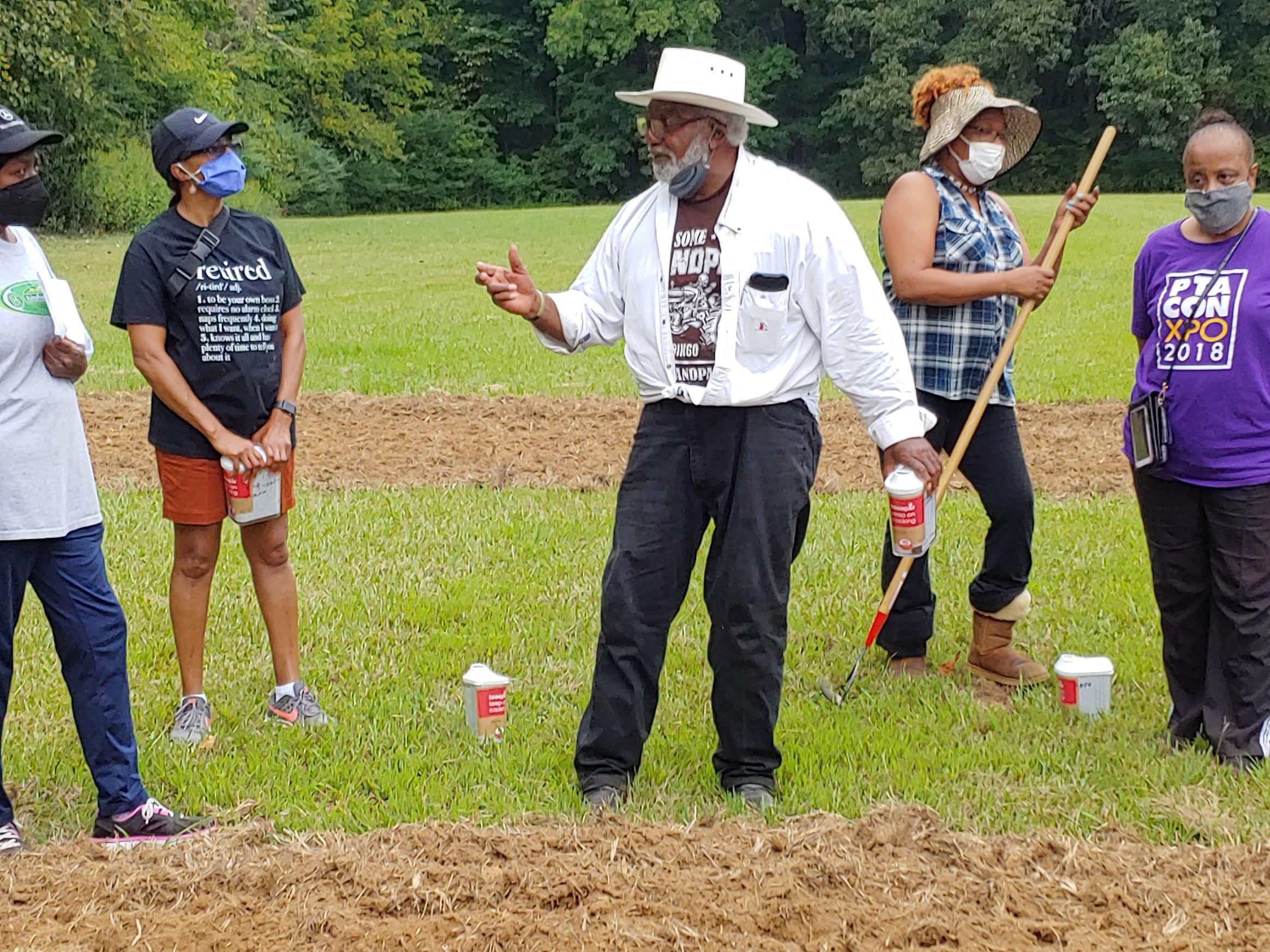 Urban gardening volunteer Ernest Trice explains planting to area residents in the new Frayser Community Garden.