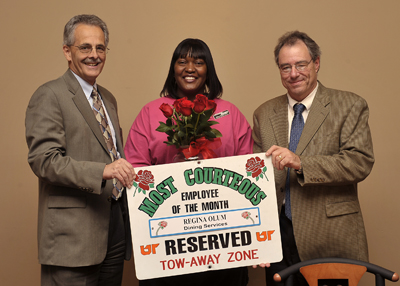 Regina Olum is presented with the October 2008 'Send Roses' award by Human Resources executive director Alan Chesney (left) and Interim Chancellor Jan Simek (right)