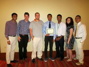 Chem-E-Car team members Nikhil Patel, co-captain Aston Thompson, William Hawks, co-captain Christian Wilson, faculty advisor Gabriel Goenaga, Megan Farell, and Dennis Edralin stand with their second-place award at the Chem-E-Car Poster Competition in Puerto Rico.