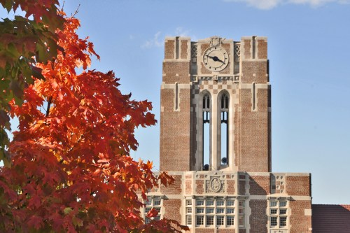 Ayres Hall tower with sunny sky and red leaves on tree, beautiful blue sky.
