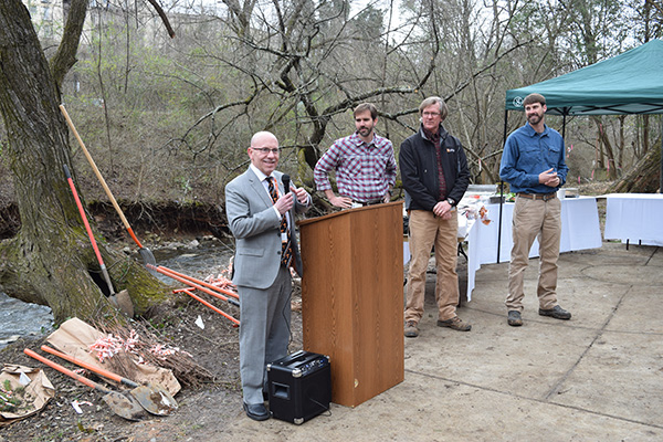 Dave Irvin, associate vice chancellor for facilities services, addresses volunteers as, left to right, Jason Cottrell, Facilities Services landscape services assistant director, Sam Adams, arborist with Facilities Services, and Garrett Ferry, stormwater coordinator, look on prior to the March 4, 2016, Arbor Day tree-planting event along Second Creek.