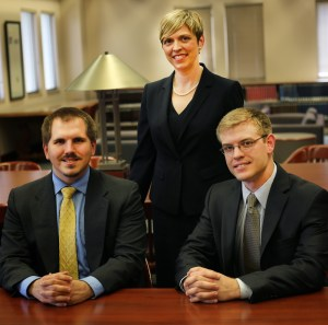 Recent UT Law graduates CJ Lewis and Thomas Smith (seated) represented Quince in his federal clemency case, with supervision from professor Joy Radice (standing).