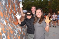 Chancellor Beverly Davenport, SGA President Morgan Hartgrove. and Student Services Director Hunter Jones pose after painting the Rock during the SGA Slap the Rock event.