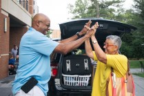 A family unloads their car at Brown Residence Hall during move-in week.