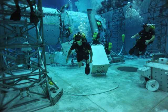 Alex Weber, center, swims through a dive tank at NASA's Neutral Buoyancy Laboratory in Houston, Texas. Weber, now a UT senior, was training NASA divers for future capsule recovery missions.