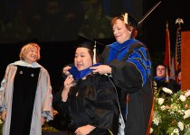 Ann Fairhurst hoods a new doctoral graduate as Susan Benner, left, looks on.