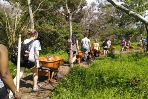Students with wheelbarrows on a trail during Alternative Spring Break.