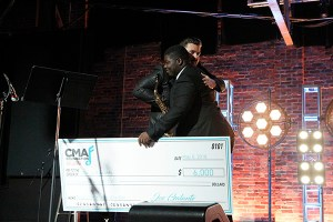 Edwards hugs country music star and CMA Foundation member Chris Young after receiving a check to pay for one of his new saxophones. (Photo courtesy of CMA)