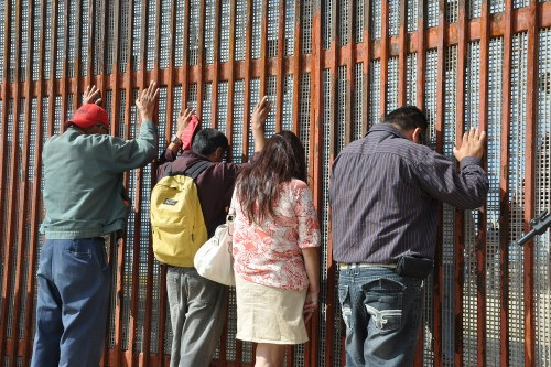 Recently deported migrants lean on a fence that separates the border between the United States and Mexico, in Tijuana. Credit: BBC World Service.