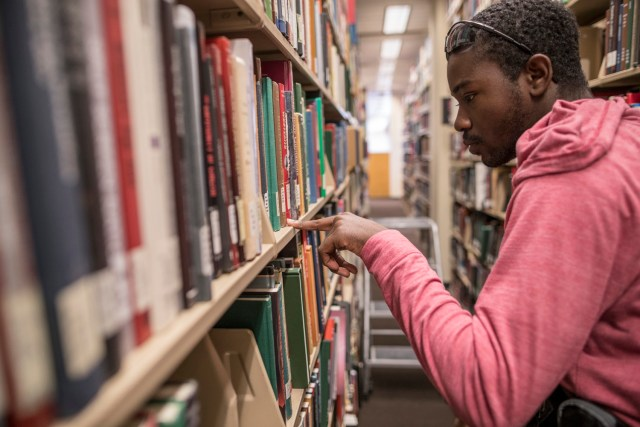 Student looking for books in John C. Hodges Library. Photo by Jack Parker