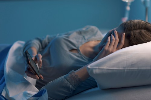 Sad sleepless patient chatting with her phone
