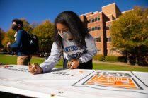 """Student signs the """"First-Generation Celebration"""" banner"""