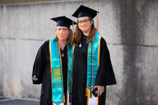 Two first-generation graduates pose together for a photo outside of Thompson-Boling Arena.