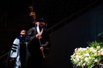 The Macebearer walks onto the stage at commencement.