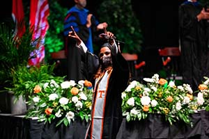 A masked graduate celebrates while walking across the stage during the 2020 commencement ceremony