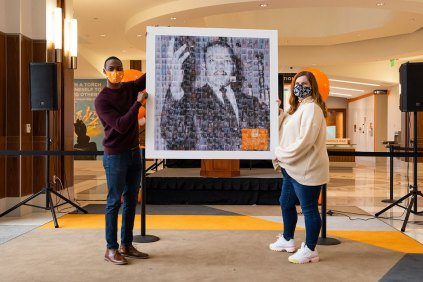 Staff members Aaron Dixon and Ronni Williams hold up the MLK photo montage, made up of photos from participants at the MLK Day celebration.