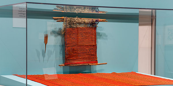 a brightly colored Navajo rug displayed in an exhibition