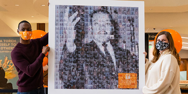 Office of Multicultural Student Life Coordinator Aaron Dixon and Assistant Director Ronni Williams hold a Martin Luther King Jr. photo collage