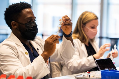 UTHSC College of Pharmacy students Olu S. Agbanigo, 3rd year, and Megan Kelly, 4th year, prepare COVID-19 vaccines in the Student Union Ballroom