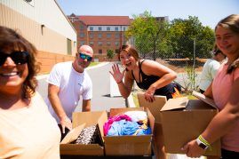 A new student waves to the camera as her family helps her move boxes into her residence hall.
