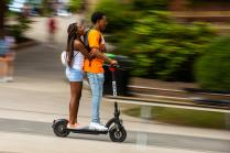 High school sweethearts from Memphis, TN ride a scooter along Pedestrian Walkway during Big Orange Friday on August 20, 2021.