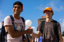 Two students fist-bump on the way to class.
