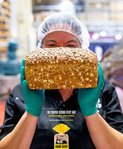 Dave's Killer Bread female factory worker poses close up with a loaf of multi-grain bread.