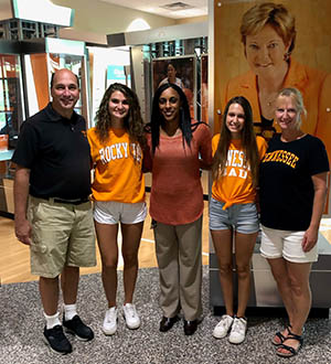 Savanna Youngquist and her dad, mom, and sister reunite with Heather Ervin. The family pose in front of a hanging photograph of Pat Summitt.