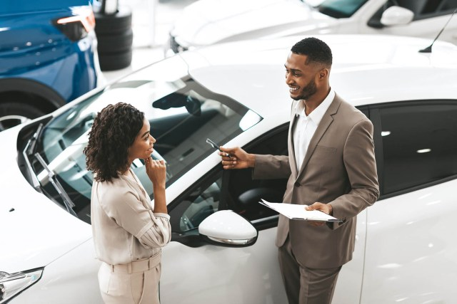 Car Sales Manager Showing Auto To Lady Standing In Dealership