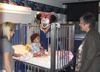 Kim Mallory with the Center for Executive Education (CEE) presents a Minnie Mouse balloon to Brionna, a patient at East Tennessee Children's Hospital, while the little girl's mother looks on. The balloons were given to CEE by Disney, and the center donated them to patients following a day-long career building program.