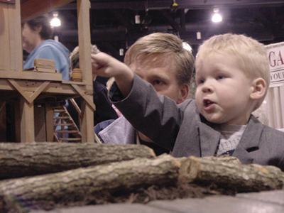 Young boy examines details of train scenes
