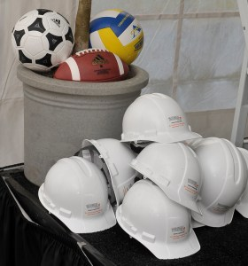 Hardhats and sports equipment on display at the groundbreaking ceremony for the new UT recreation fields