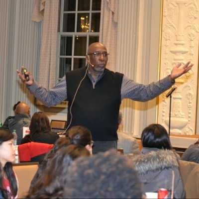 Photo: Tony Porter, arms outstretched, speaking to audience