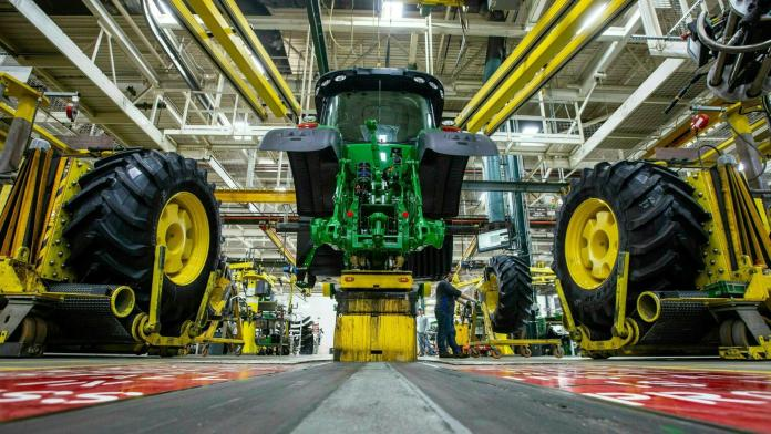 In this April 9, 2019, wheels are attached as workers assemble a tractor at John Deere's Waterloo, Iowa assembly plant. (Zach Boyden-Holmes / Telegraph Herald via AP, File)