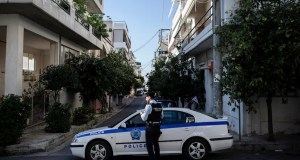 Greek police block the road as investigators inspect the scene
