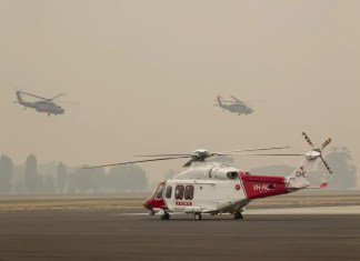 Two Australian Army Blackhawk helicopters flying through smoke haze at RAAF Base East Sale at RAAF Base East Sale in Sale, during bushfire relief efforts