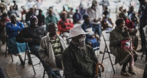 An elderly man at a Sassa pay-point in Soweto covers his mouth while queuing