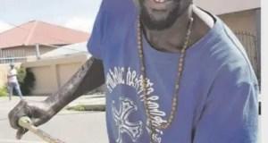 Homeless Johannesburg beggar Simon Kekana ties his cup onto a stick