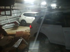 Driver injured after driving through garage wall