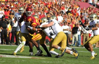 Too much Trojan: USC running back Justin Davis pulls a horde of Notre Dame defenders with him. Photo Credit: Dennis J. Freeman/News4usonline.com