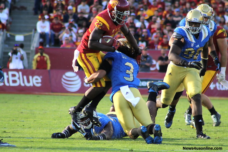 USC running back Justin Davis (22) tries to go high and over UCLA's Randall Goforth. Photo by Dennis J. Freeman/News4usonline.com