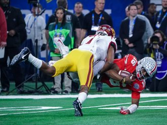USC defensive back Marvell Tell (7) gets a solid hit on Ohio State quarterback J. T. Barrett (16) in the 82nd Annual Goodyear Cotton Bowl Classic. Photo by Michael Lark for News4usonline