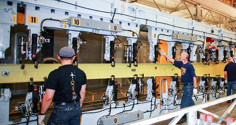 Operadores de grua Bin Pham, Marty Deslauriers e Larry Freeman carregam as partes iniciais das longarinas do 737 Max, numa maquina robotizada de montagem de longarinas.
