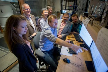 Photo - AQT team members examine the latest performance of a new scalable control system. From right to left: Anastasiia Butko, Jonathan Carter, Gang Huang, Machiel Blok, Miro Urbaneck, Irfan Siddiqi, and Dar Dahlen. (Credit: Peter DaSilva/Berkeley Lab)