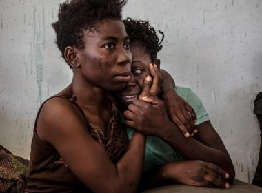 Two Nigerian refugees cry and embrace in a detention centre for refugees in Surman, Libya, August 2016 Reuters