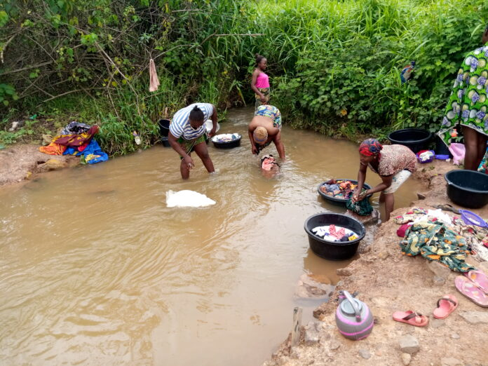 Women washing at the polluted Onupi River. Photo Credit: The News Digest