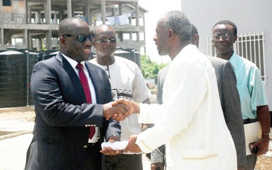 Alhaji Collins Dauda (in smock), the Minister of Water Resources, Works and Housing, officially handing over the documents on the houses at Borteyman to Mr Ernest Thompson (left), the acting Director-General, SSNIT.