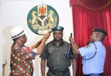 Chief Willie Obiano, Governor of Anambra State (l) and Mr. Hosea Karma, Anambra State Commissioner of Police decorating Mr. Phillip H Ezekiel at the Governor's Lodge, Amawbia.