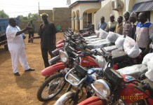 Mr Daniel Bugri Naabu, (right) Northern Regional Chairman of the New Patriotic Party (NPP) presenting keys to the motorcycles to one of the NPP Chairmen from the constituencies